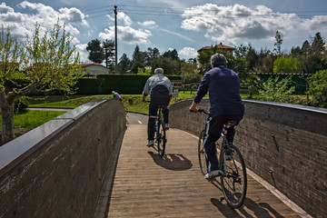 Some cyclists ride the park cycle path on a sunny spring day.
