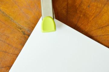 stapler pushing white paper on wooden table