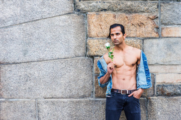 Young East Indian American Man wearing blue fashionable Denim jacket, opened, showing half naked strong body, black jeans, holding white rose, standing by rock wall in New York, waiting, thinking..