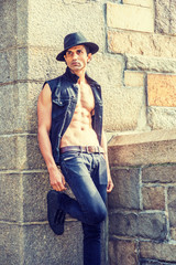Young East Indian American Man wearing black sleeveless fashionable Denim jacket, unbuttoned, showing half naked body, jeans, Fedora hat, standing by rock wall and fence in New York, looking away..