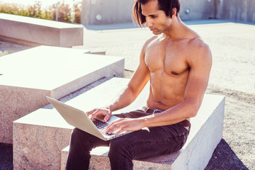 Young East Indian American Man, half naked, showing strong body, wearing black jeans, sitting on stone bench at park in New York under sun, looking down, working laptop computer..