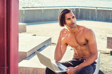 Young East Indian American Man, half naked, showing strong body, wearing black jeans, sitting on stone at park in New York under sun, working laptop computer, looking up, thinking..