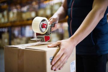 Male warehouse worker sealing cardboard boxes.