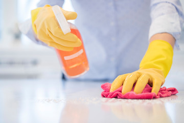 Close Up Of Woman Using Spray Polish To Clean Kitchen Surface