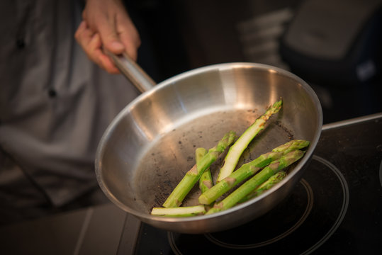 Preparing green asparagus in frying pan
