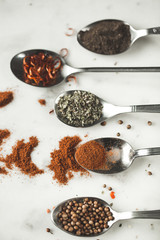 Spices in different spoons on stone marble table background. Rustic vintage color toning. Closeup macro photo.