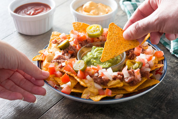 People eating mexican nachos with beef, guacamole, cheese sauce, peppers, tomato and onion in plate on wooden table