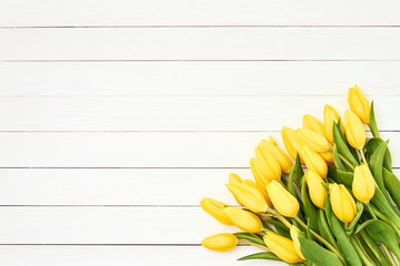 Yellow tulips bouquet on white wooden background. Holiday background. Copy space, top view.