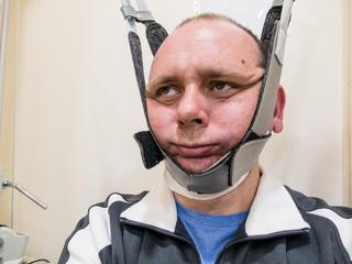 Man in neck traction machine