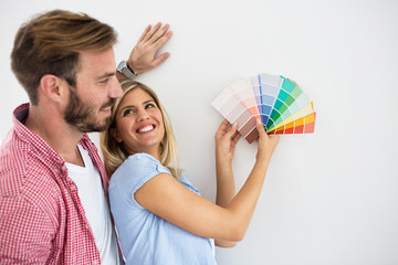 Young happy couple choosing colors