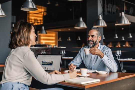 Businessman and businesswoman drinking coffee at cafe and smiling.