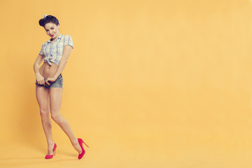 beautiful girl in pin-up style on a yellow background in red shoes