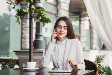 Young businesswoman talking on phone outdoors