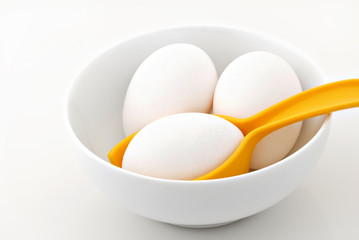 Three eggs in a bowl with one egg resting in an egg holder.