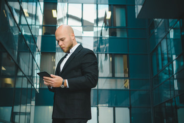 Businessman using tablet in front of office