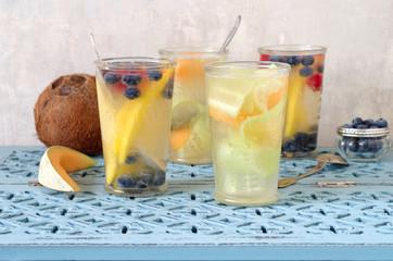 verschiedene aromatisiertes Kokoswasser mit Mango, Blaubeeren und Himbeeren und mit Gurke und Cantaloupe Melone