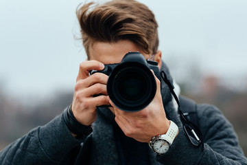 Close up view of young photographer taking photos in the city. Dressed in warm jacket, white watches.