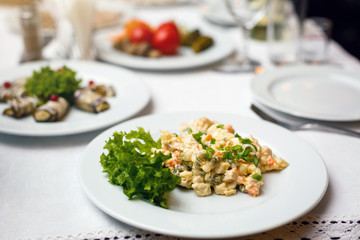 Traditional Russian Salad also called Olivier salad on a vintage wooden table