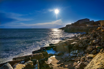Beautiful seascape outside the city of Sete (Sète) on southern France. Evening sun lights the sea, beach and rocks