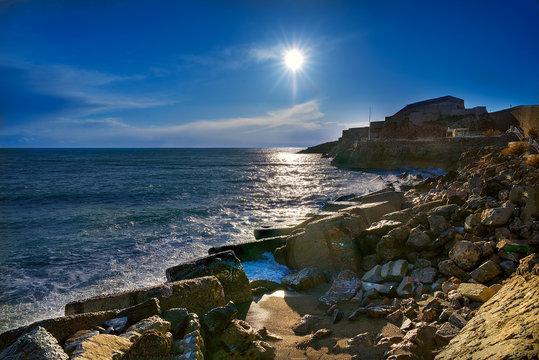 Beautiful seascape outside the city of Sete (Sète) on southern France. Evening sun lights the sea, beach and rocks