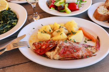 Cooked fresh red scorpionfish sarved with boiled potatoes in the greek tavern.