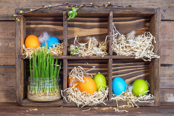 Happy easter holiday concept. Colorful chicken eggs quail eggs germinated wheat in glass jar branch of trees with buds.