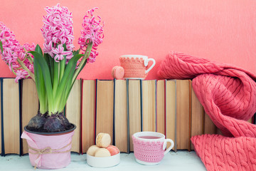 Pink hyacinths, macaroons, tea cups and scarf near pile of books at pink background. Beautiful spring pink background. Copy space.