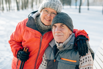 Senior couple embracing in winter snowy park. Mature woman and smiling old man hugging looking at camera.