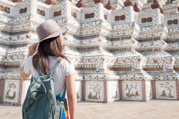 Rear view of young woman travelling at Wat arun in Bangkok, Thailand