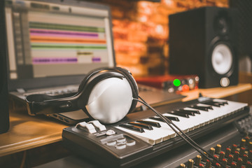 computer music, home studio equipment. headphone on midi keyboard synthesizer with laptop computer and loudspeaker monitor