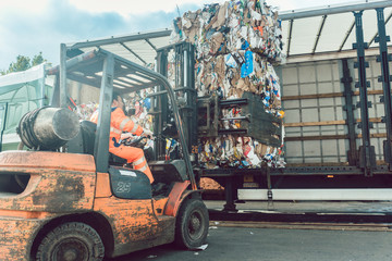 Worker loading separated waste on truck for recycling