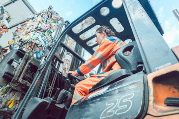 Female worker on forklift loading separated garbage on truck