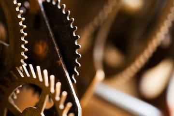 Rusty metal clock mechanism cog gears connection concept. Black iron wheels industrial still life photo. Macro view, selective focus.