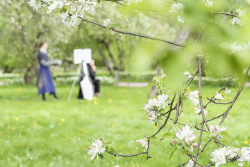 Girl paints painting on canvas of easel in park with blooming sakura. Blurred image for spring creative background