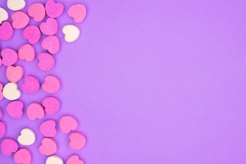 Candy sugar hearts side border on a pastel purple paper background