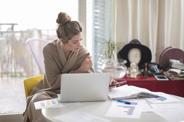 Young beautiful woman works on computer from a home with a laptop on a white desk as a freelancer.Self-employment concept