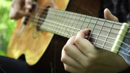 Girl playing music on acoustic guitar.