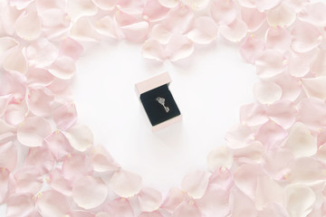 romantic gift surrounded by pink rose petal heart