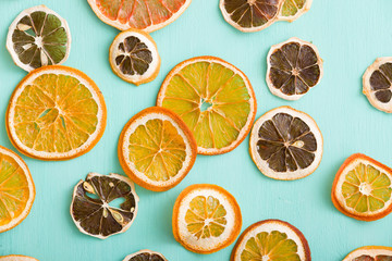 Top view on dried citrus chips: orange, lemon and grapefruit on turquoise background.