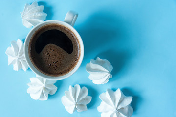 White cup of coffee with foam on a blue background with white meringues. Breakfast, dessert. Close up. Flat lay