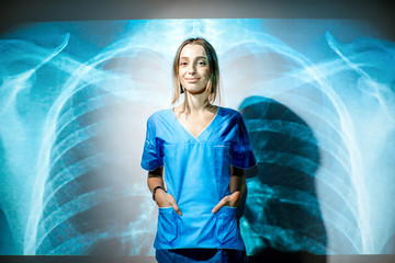 Portrait of a young woman nurse in uniform with projected x-ray of human lungs