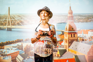 Portrait of a young woman traveler with photocamera with projected image of Riga cityscape