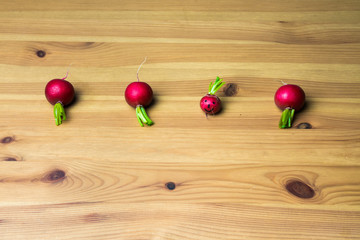 Four red radishes in a row on a wooden table - one is happy