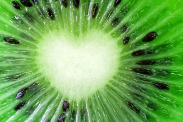 Kiwi fruit fresh natural close-up. Heart shape. Cut the pieces of the macro. Green background.