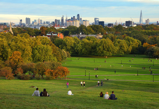 People resting on Primrose Hill at sunset, London, UK