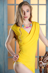 Portrait of attractive young adult girl with long beautiful blond hair and athletic slender figure elegantly posing in short yellow dress near an old chair.