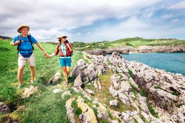 Couple backpacker travelers walk on ocean rocky coast. Asturias. Spain