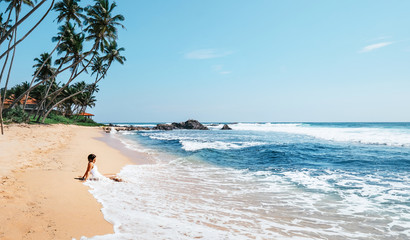 Woman enjoy with ocean surf sitting on the lonely tropical beach under the palm trees