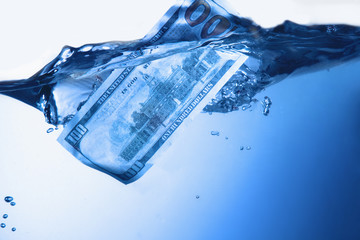 Money concept showing US Dollar sinking in шатер as a symbol of global economic crisis