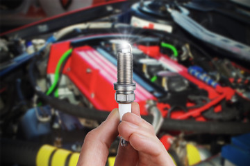 Mechanic holds a spare part spark plug in his hand. Auto part spark plug close-up.
